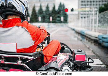 Karting racer, go kart driver in helmet, back view. Carting...