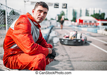 Karting racer sits on a tire, kart on background, outdoor...