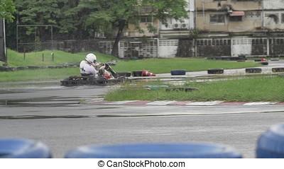 karting, -, treiber, in, helm, auf, kart, circuit., erwachsener, kart, racer, auf, track., regnerisches wetter, auf, der, rennen, track., zeitlupe
