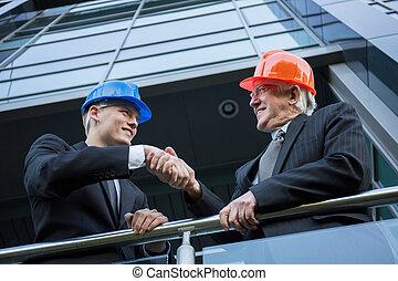 kaski, inżynierowie, potrząsające ręki