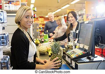 kassierer, besitz, ananas, an, prüfung kostenzähler, in, supermarkt