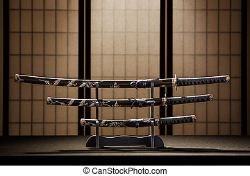 Katana, wakizashi and tanto on stand in a room, yellow ...