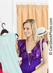 kaukasisch, blonde , kijkende vrouw, op, een, hemd, in, een, klerenopslag