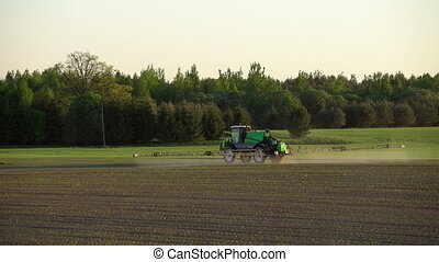farm tractor spraying fertilize wheat field