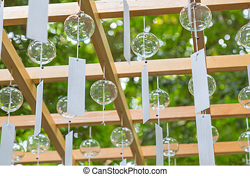 Clear glass wind chimes hang from wood structure during Wind...