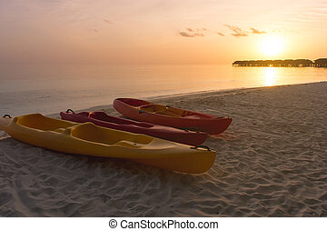 Kayak at the tropical beach at beautiful sunset. Silhouette beautiful tropical Maldives resort hotel and island with beach and sea on sunset sky for holiday vacation background concept.