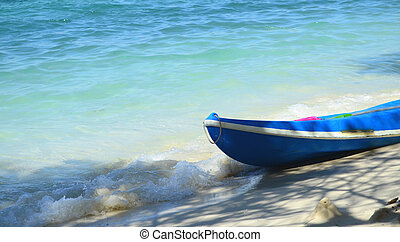 Kayak boat on the beach with blue sea
