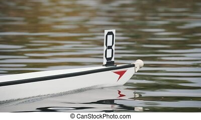 Kayak bow with number eight moving slowly on the river...