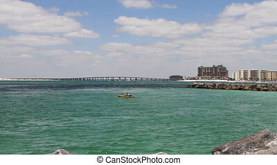 Lone man in a kayak paddles out into the water to fish in pass at the jetty in Destin, Florida.