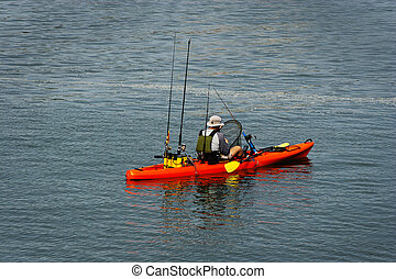 orange kayak, yellow paddles, with fishing poles in the back. Mam with his back to the camera holding a net getting ready to pull up a fish.