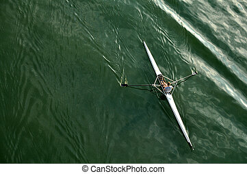 Kayak - image of a young man rowing in kayak down the river