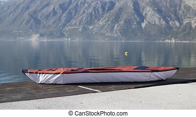 Kayak lies on the shore. Wooden jetty. Bay of Kotor in Montenegr