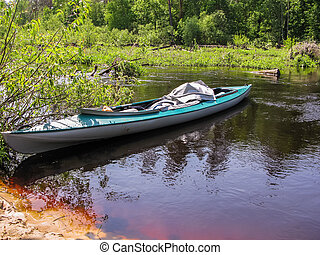 Kayak on the surface of the river near the shore.