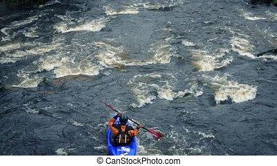 Kayak Passes On Big River - Man in kayak paddles past on...