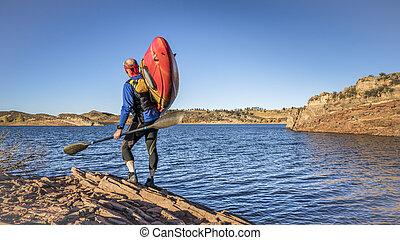 kayak portaging on lake shore - portaging and launching ...