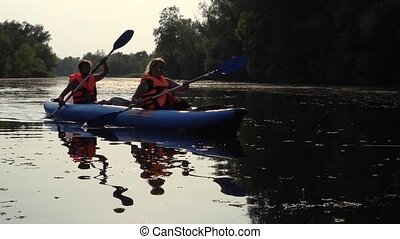 Kayak with a guy and a girl swims on the river . Slow motion...