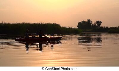 Kayak with people at dusk. Slow motion - Kayak with people...