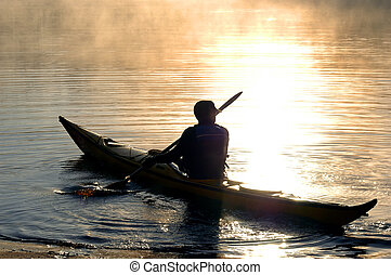 Kayaker at dawn - A kayaker is silhouetted against the...