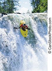 Kayaker in rapids coming over waterfall (selective focus)