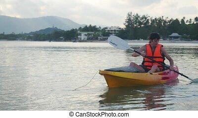 Kayaker is sitting on kayak floating and water splashing....