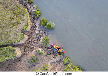 kayaker on a muddy shore of Dismal River