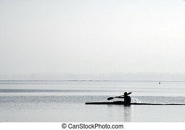 Kayaker on kayak on Annecy lake, back light, silhouette and...