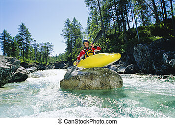 Kayaker on top of rock in rapids smiling