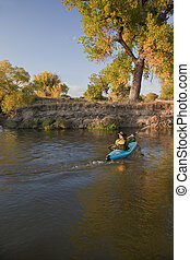 kayaker paddling across a river - kayaker (fifty five years...