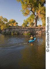 kayaker paddling across a river