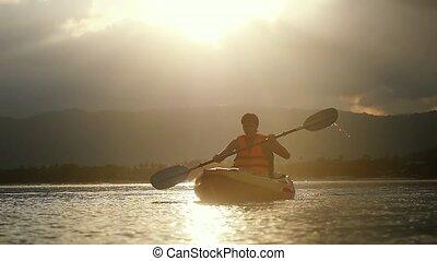 Kayaker paddling at amazing sunset and water droplets...