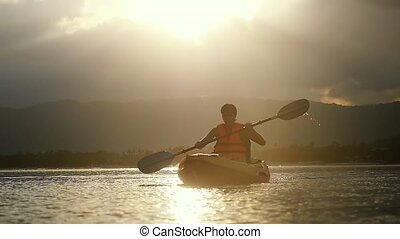 Kayaker paddling at amazing sunset and water droplets...