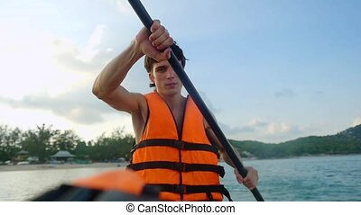 Kayaker traveler paddling on tropical island in sunny day...