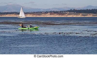 Kayakers glide across water in slow-motion