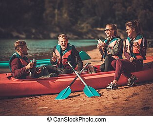 Kayakers having snack on their boat