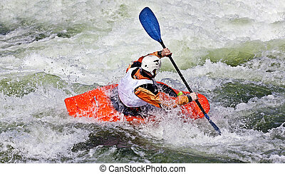 kayaking - an active male kayaker rolling and surfing in...