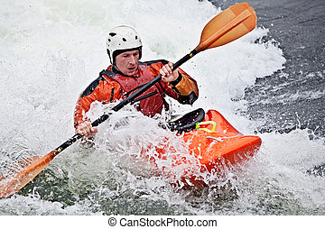 kayaking - an active male kayaker rolling and surfing in ...