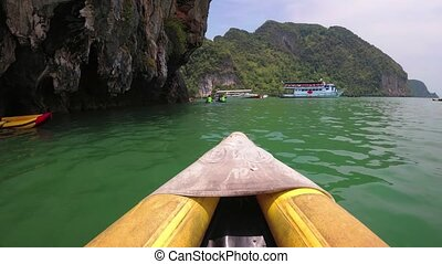 Kayaking through peaceful green sea waters, beneath overhanging limestone cliffs, from an onboard perspective, in Phang Nga Province, Thailand.