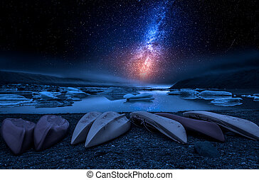 Kayaks and the glacier lake at night with stars, Iceland