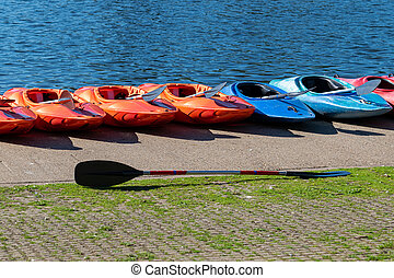 Kayaks lined up on a the bank of a lake