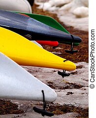 Kayaks in different colors lined up on the beach, with some...