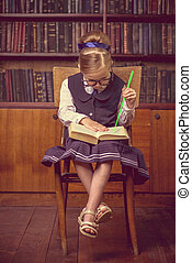 keen on reading - Cute girl looks curiously into the book in...