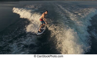 Keep Balance - Above view of athletic man riding surf