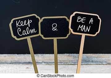 Keep Calm and Be A Man message written with chalk on mini blackboard labels