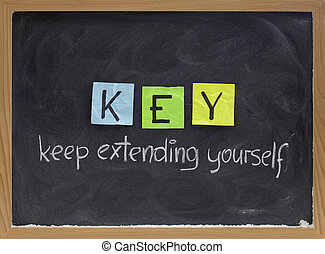 KEY (keep extending yourself) - coaching, motivational, self development acronym, white chalk handwriting and colorful sticky notes on blackboard