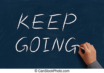Keep Going on blue chalkboard with the hand of businessman.