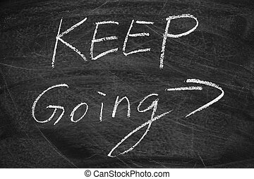 Keep Going on the blackboard with chalk writing.