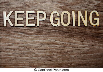 Keep Going on wooden background business concept