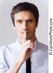Keep it between us! Confident young man in white shirt looking at camera and holding finger on lips while standing against grey background