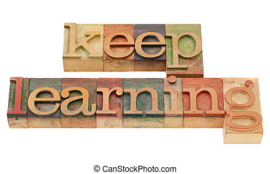 continuous education concept - keep learning words in vintage grunge wood letterpress printing blocks, isolated on white