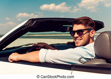 Keep on driving. Rear view of happy young man looking over shoulder and smiling while driving his white convertible
